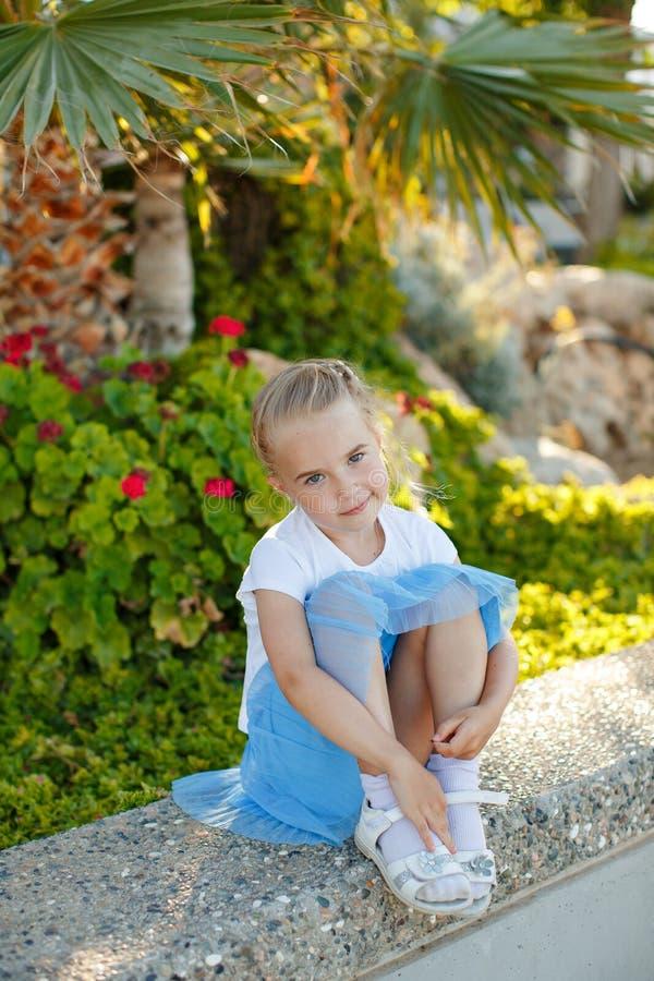 美丽的白肤金发的女孩在一条蓝色裙子的5岁在背景 库存图片