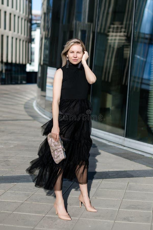 美丽的白肤金发的女孩在与一台传动器的一件黑晚礼服站立在一个现代大厦的背景 免版税图库摄影
