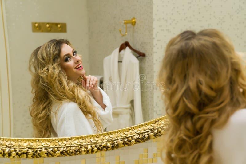 美丽的白肤金发的女孩在她的卫生间里改正她的头发和看在镜子 秀丽少妇改正她的头发 库存照片