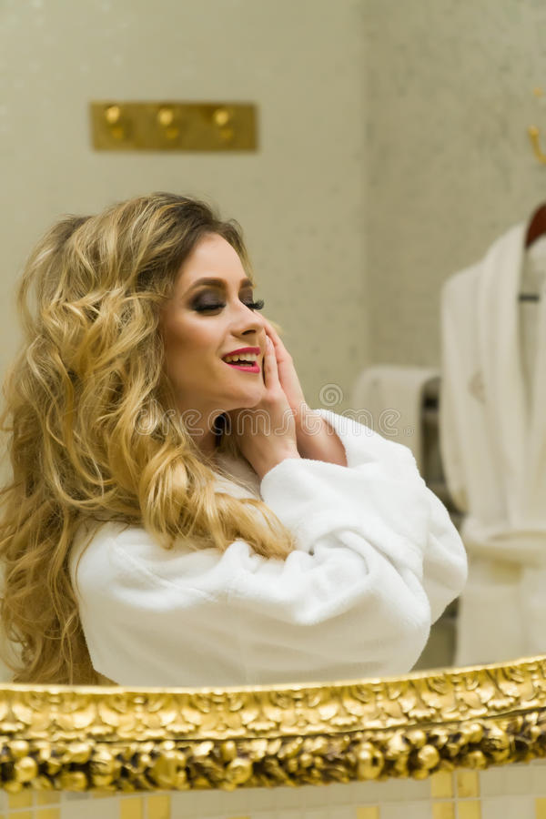 美丽的白肤金发的女孩在她的卫生间里改正她的头发和看在镜子 秀丽少妇改正她的头发 免版税库存图片