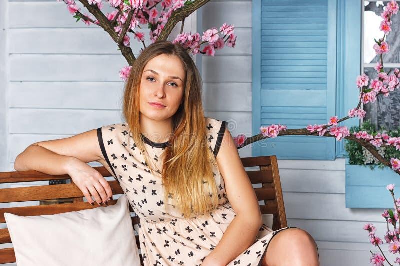 美丽的白肤金发的女孩在春天樱桃庭院里 库存照片