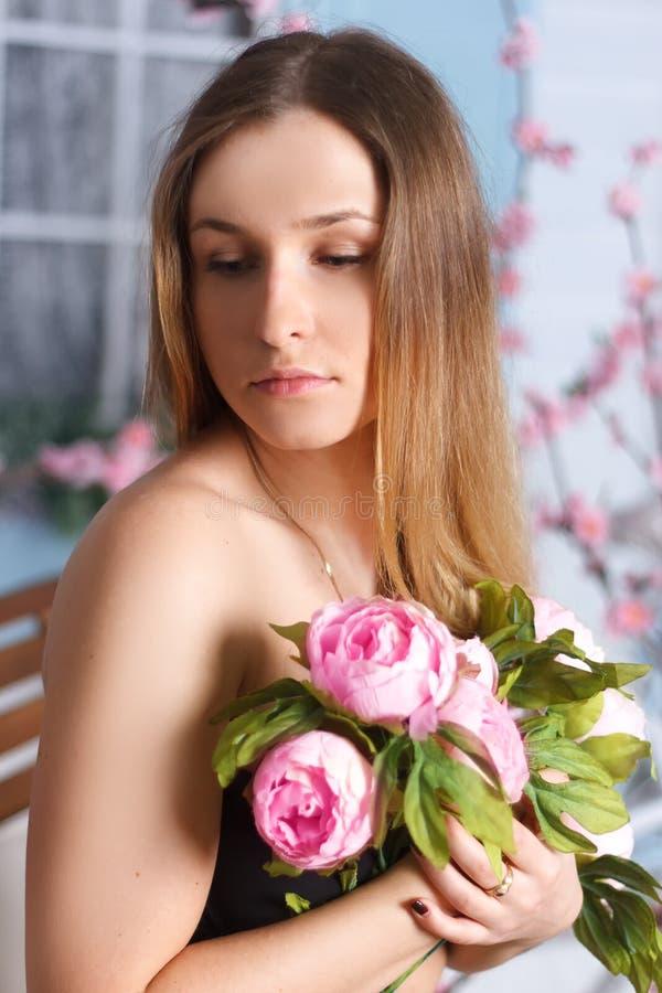 美丽的白肤金发的女孩在春天樱桃庭院里 免版税库存图片