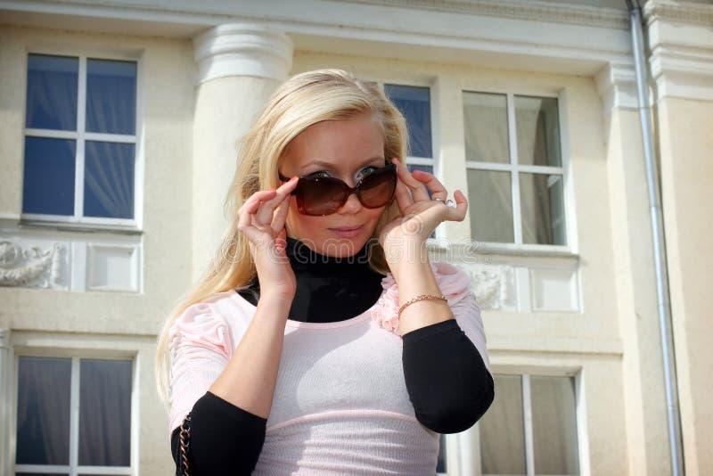 美丽的白肤金发的女孩太阳镜 图库摄影