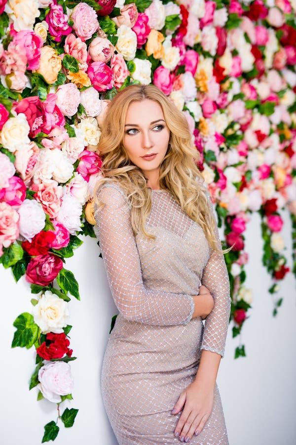 美丽的白肤金发的女孩画象礼服的在五颜六色的花 免版税库存图片