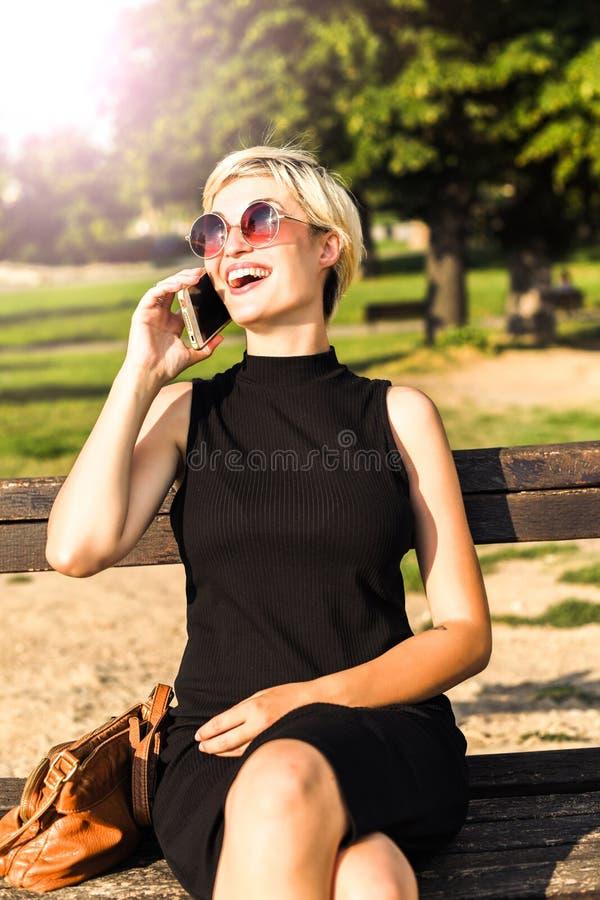 美丽的白肤金发的女孩谈话在电话和微笑 免版税库存图片