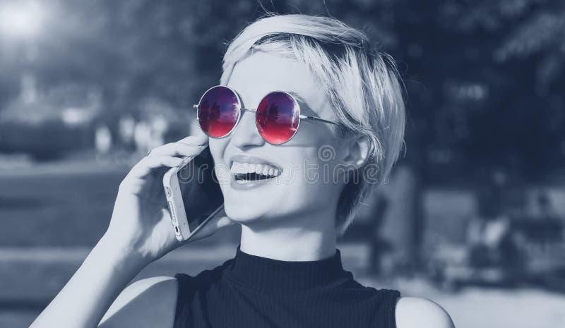 美丽的白肤金发的女孩谈话在电话和微笑 库存照片