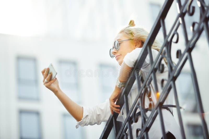 美丽的白肤金发的女孩采取在她的智能手机的selfie 逗人喜爱的妇女自画象在前面照相机电话的 库存照片