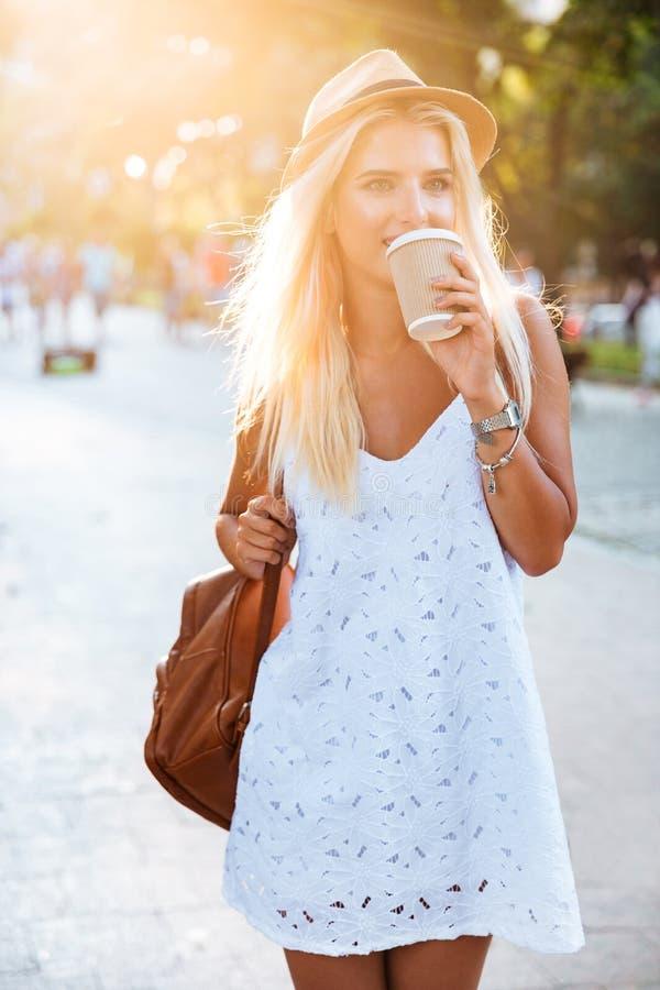 年轻美丽的白肤金发的女孩饮用的咖啡从拿走杯子 免版税图库摄影