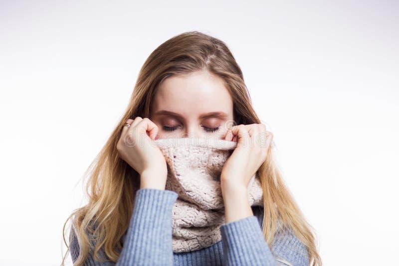 美丽的白肤金发的妇女冬天画象毛线衣和围巾的在白色背景 女孩用妇女发网盖她的面孔并且关闭 免版税库存图片