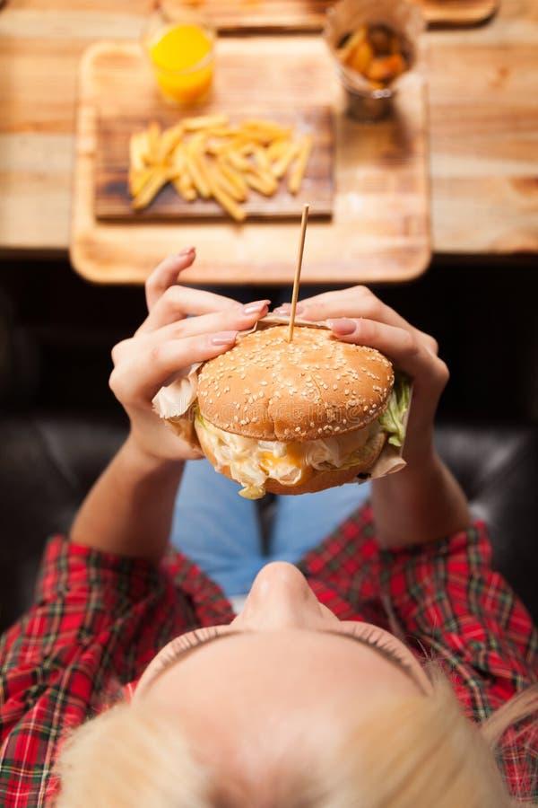 美丽的白肤金发的妇女吃牛肉汉堡油罐顶部角钢视图 库存图片
