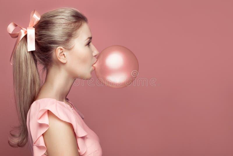 美丽的白肤金发的妇女吹的胶 方式纵向 免版税库存图片