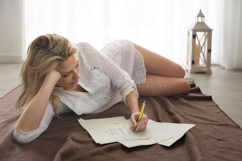 美丽的白肤金发的妇女在地板和凹道设计skeches用手放置 免版税图库摄影