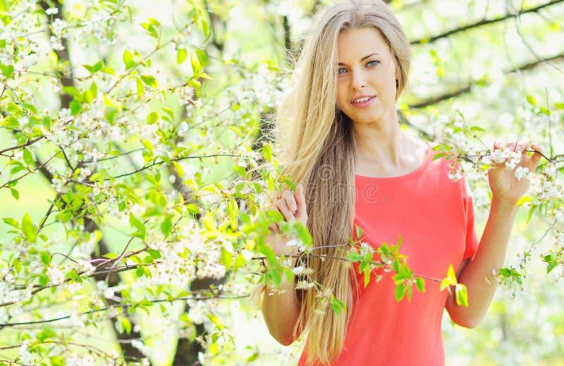 美丽的白肤金发的妇女在开花的庭院里 库存图片