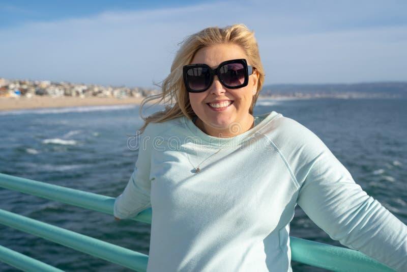 美丽的白肤金发的妇女在曼哈顿比奇加利福尼亚码头摆在下午阳光末期 图库摄影