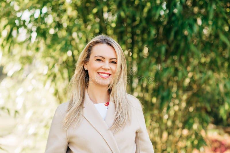 美丽的白肤金发的妇女室外画象  库存照片