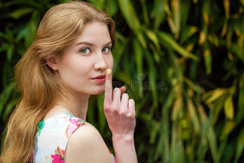 年轻美丽的白肤金发的妇女投入了食指到嘴唇作为标志 免版税库存图片