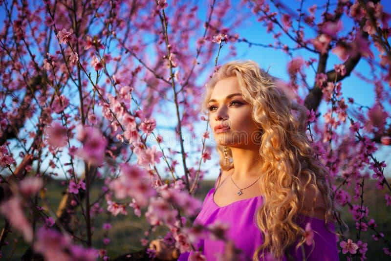 美丽的白肤金发的妇女画象开花的玫瑰园,春天心情好日子 免版税库存图片