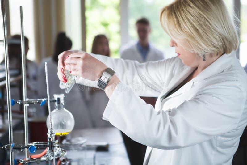 年轻美丽的白肤金发的妇女研究员化学家物质为与实验室盘的化工用途做准备 做ch的药剂师 免版税库存照片
