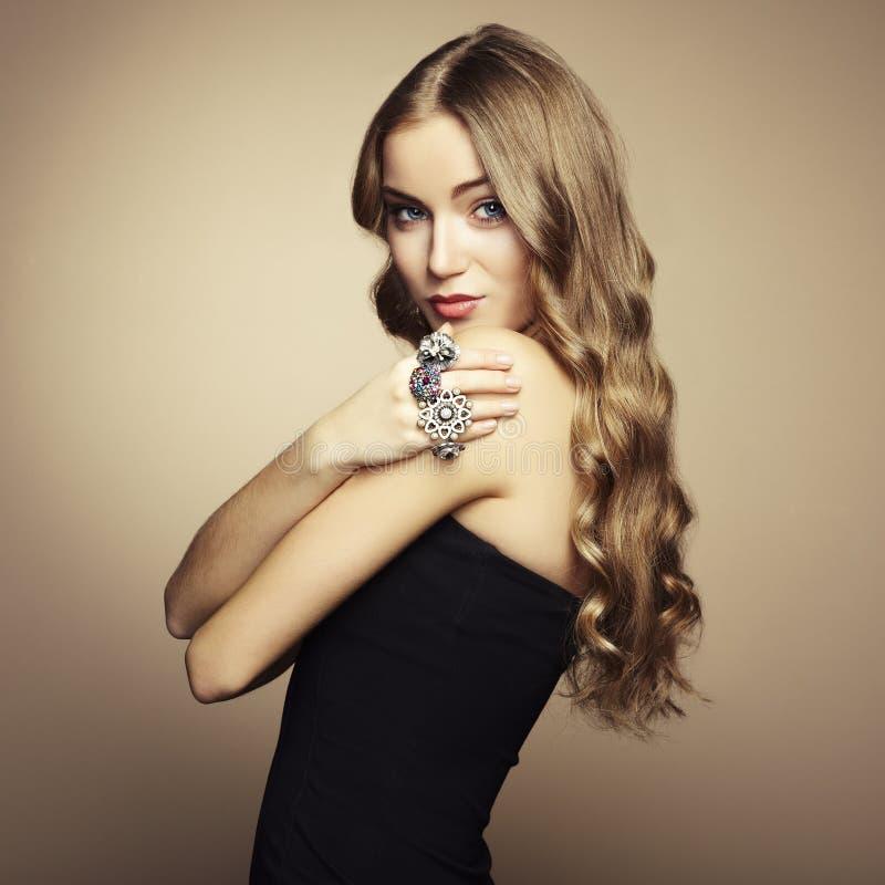 美丽的白肤金发的妇女纵向黑色礼服的 免版税库存图片