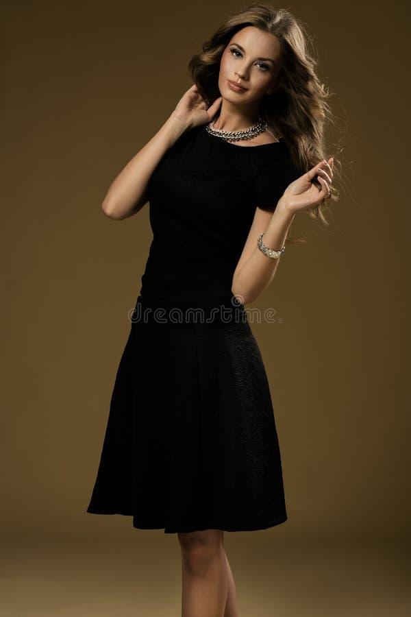 美丽的白肤金发的妇女纵向黑色礼服的 免版税图库摄影