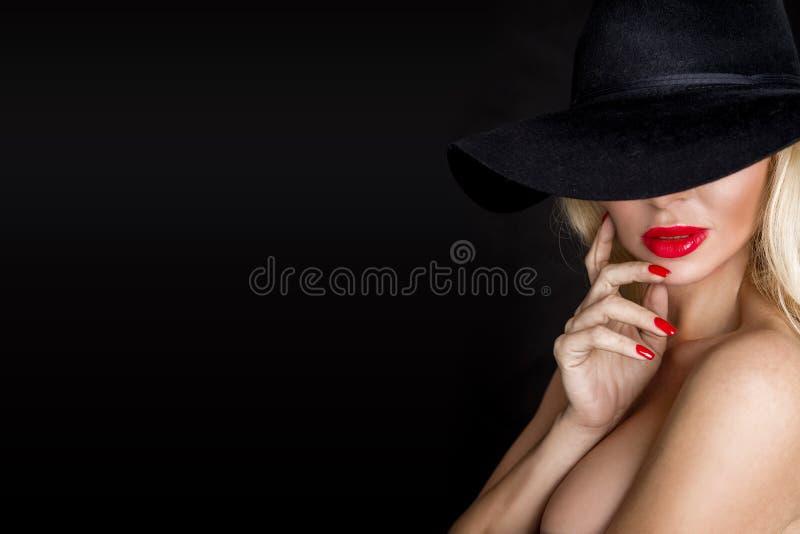 美丽的白肤金发的妇女,性感的模型与红色嘴唇,穿戴在黑女用贴身内衣裤成套装备身体泳装和黑帽会议 免版税图库摄影