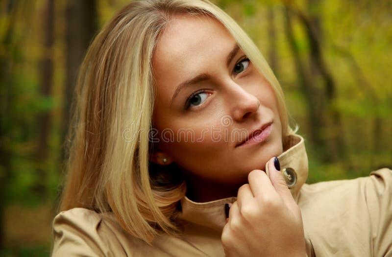 美丽的白肤金发的妇女画象在森林里有绿色和黄色树背景 免版税库存照片