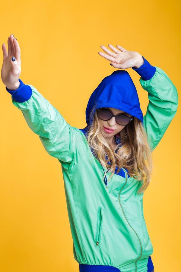 美丽的白肤金发的妇女画象太阳镜和蓝绿色戴头巾夹克的在黄色背景 行家夏天 图库摄影