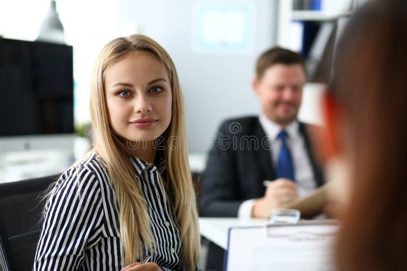 美丽的白肤金发的干事在看在照相机的办公室 免版税库存照片