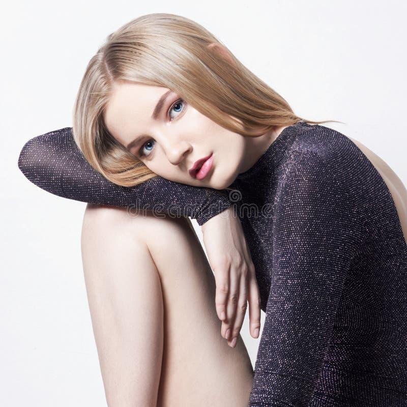 美丽的白肤金发的性感的妇女 有完善的身体的女孩坐凳子 美好的长的头发和腿,光滑的干净的皮肤,护肤 免版税库存图片