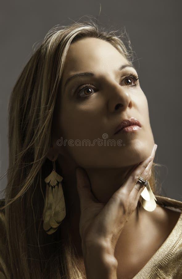 美丽的白肤金发的成熟妇女画象黄金储存的她的对她的喉头的手 免版税图库摄影