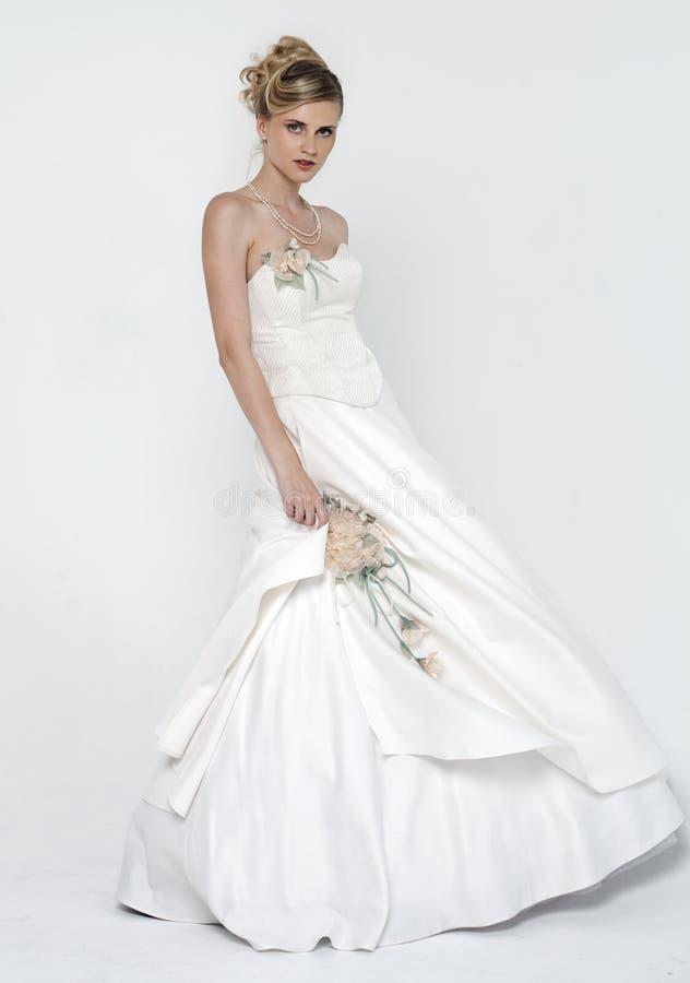 美丽的白肤金发的新娘佩带的婚礼礼服 免版税库存图片