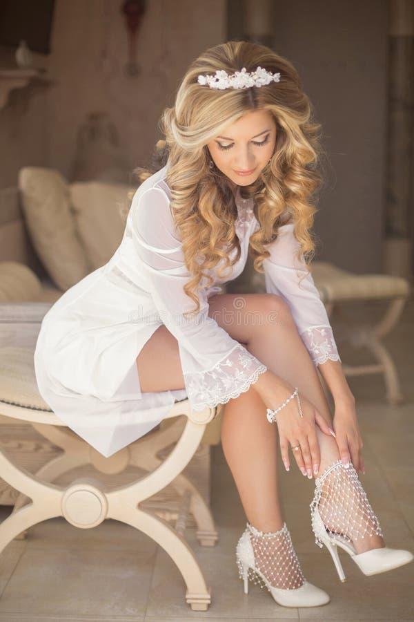 美丽的白肤金发的新娘佩带的白色婚礼鞋子,有古芝的女孩 免版税库存图片
