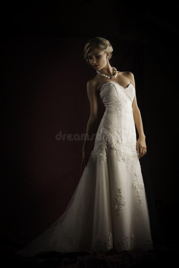 美丽的白肤金发的新娘佩带的葡萄酒无背带的婚礼服 库存照片