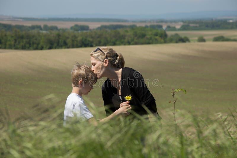 美丽的白肤金发的母亲亲吻她的甜儿子,给花 免版税库存图片