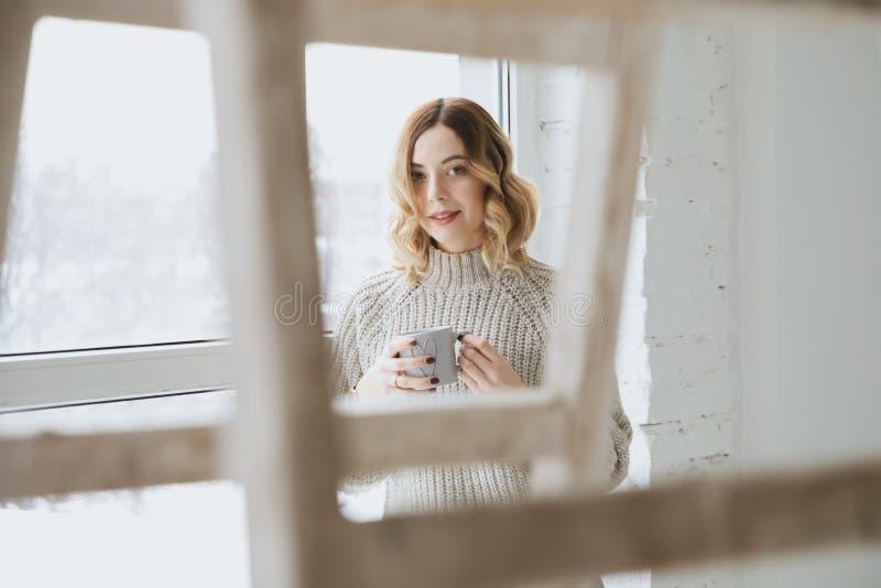 美丽的白肤金发的由窗口的女孩饮用的茶 免版税库存图片