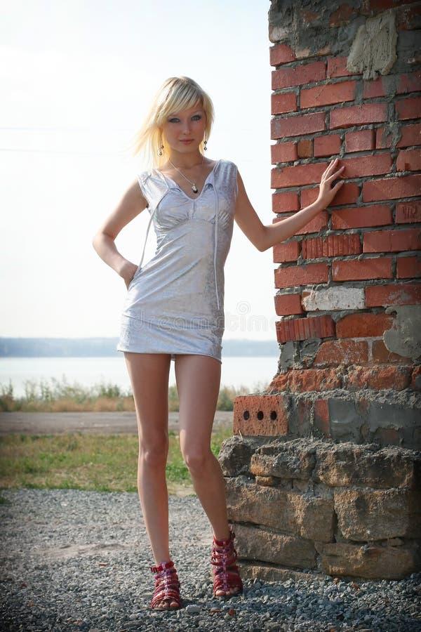 美丽的白肤金发的砖女孩墙壁 免版税图库摄影