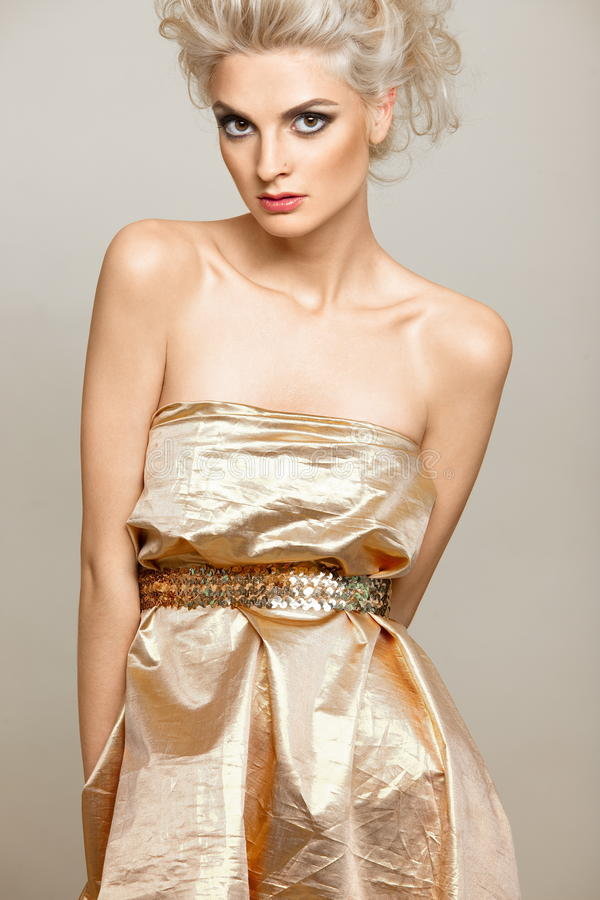 美丽的白肤金发的礼服金子 免版税库存图片