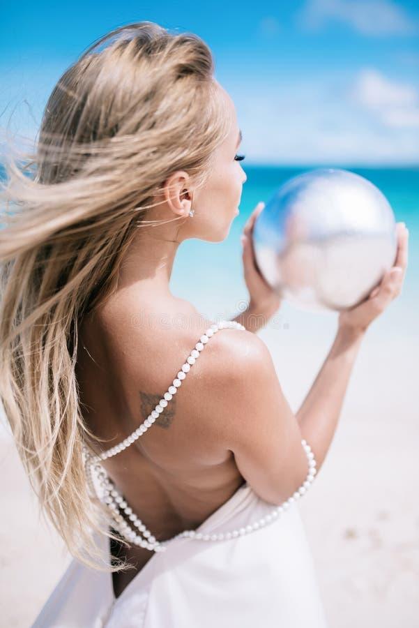 美丽的白肤金发的长的头发新娘的Ortrait一个开背部婚礼礼服立场的在与珍珠的白色沙子海滩 免版税库存照片