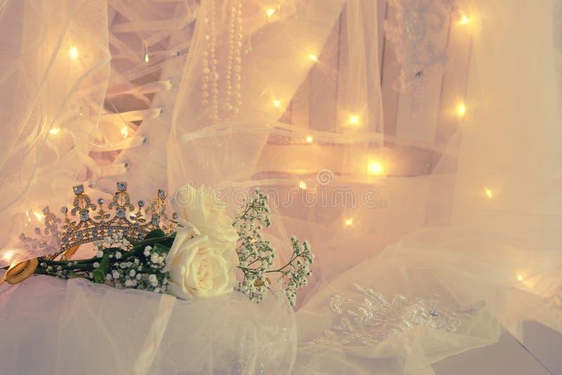 美丽的白色婚礼礼服、冠状头饰和面纱在椅子与金诗歌选点燃 库存图片