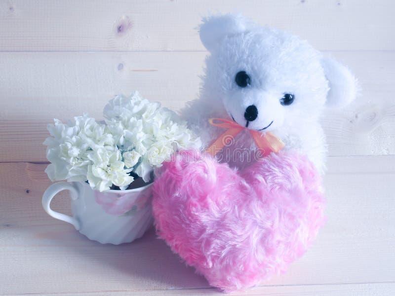 美丽的白色康乃馨在有软的桃红色心脏的可爱的茶杯开花在木背景 免版税库存图片