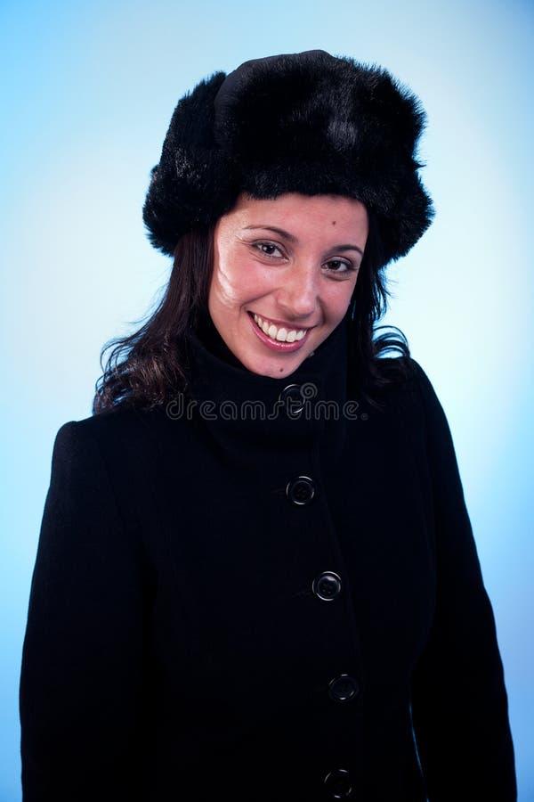 美丽的盖帽外套微笑的妇女 免版税图库摄影