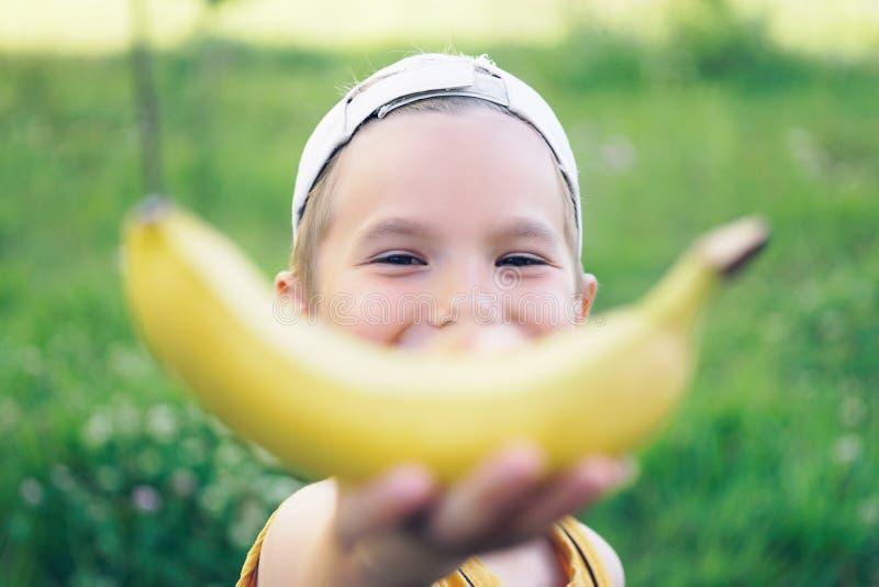 美丽的盖帽的年轻人微笑的白种人男孩有在自然背景的香蕉微笑的 库存照片