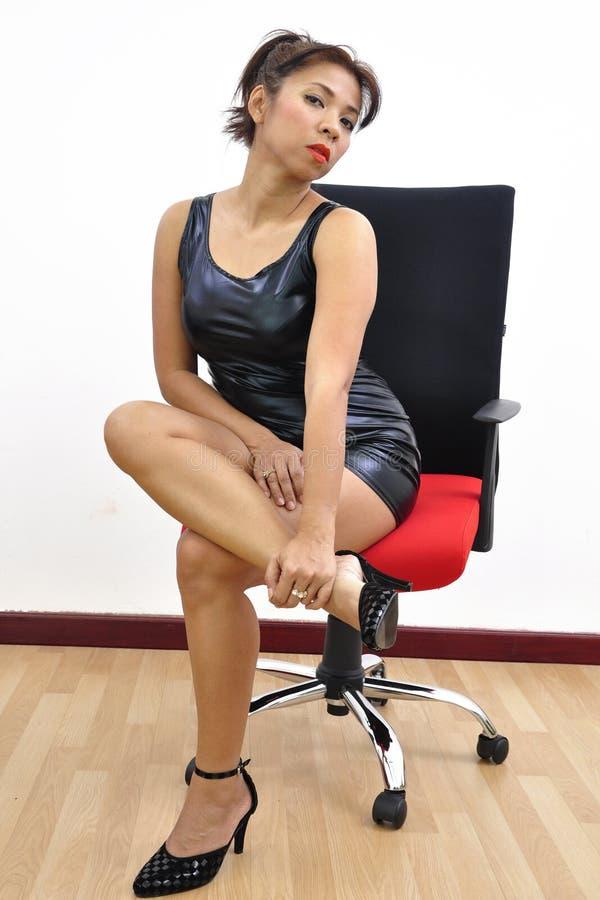 美丽的盘的妇女性感的黑礼服腿 库存照片