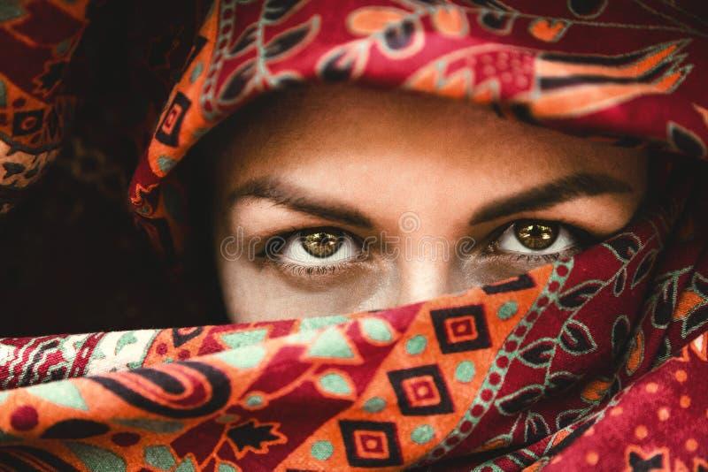 美丽的眼睛 一名妇女的面孔一条红色印度围巾的 传神神色 东方秀丽 免版税库存照片