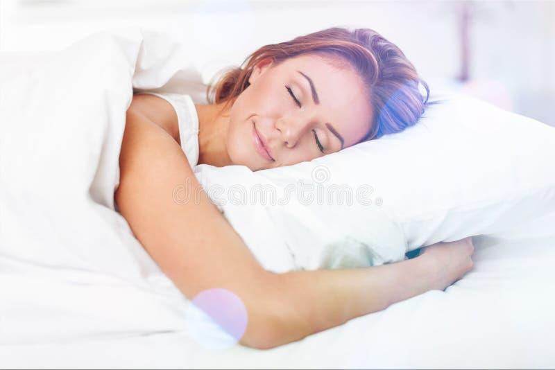 美丽的睡觉的妇女在与火光的白色床上 免版税库存照片