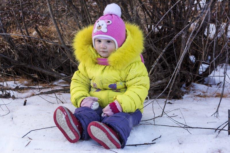 美丽的矮小的婴孩在新鲜的雪的开会在一个晴朗的冬日 免版税库存照片