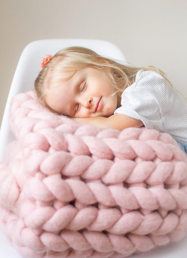 美丽的矮小的愉快的白肤金发的姜女孩坐与一条桃红色美利奴绵羊的羊毛毯子的床 库存图片