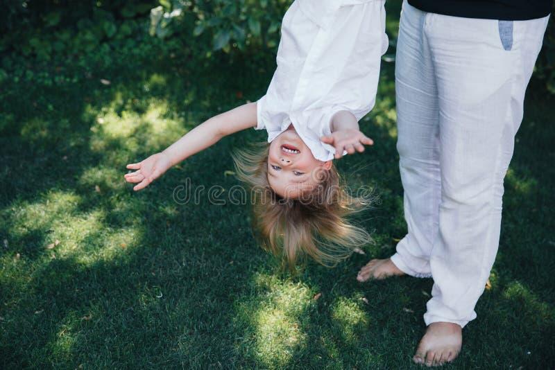 美丽的矮小的白肤金发的女婴有使用愉快的乐趣的笑容在有她的爸爸、孩子和父亲的一件白色礼服 图库摄影