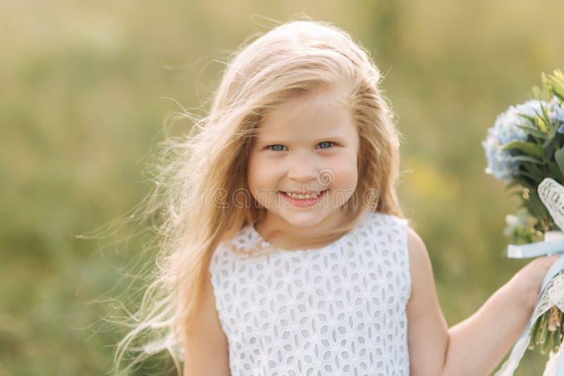 美丽的矮小的金发女孩画象领域的 在大树和举行花束前面的女孩立场 免版税库存照片