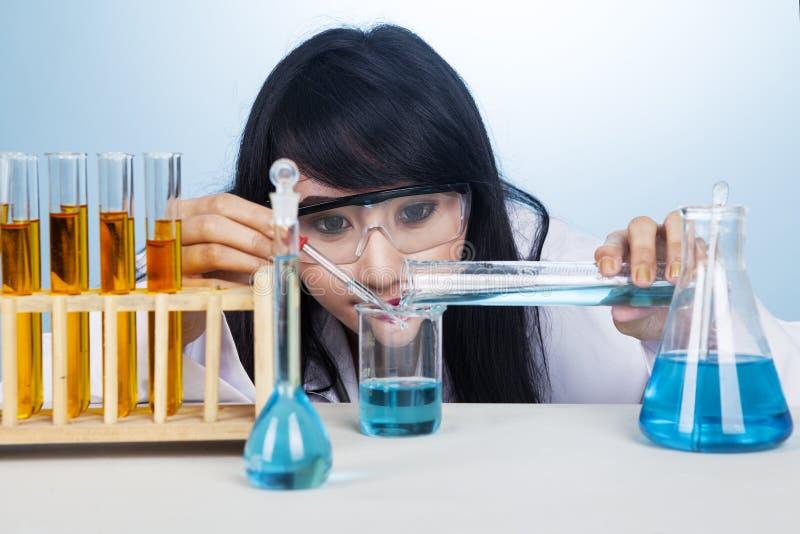 有化学制品的可爱的研究员 免版税图库摄影